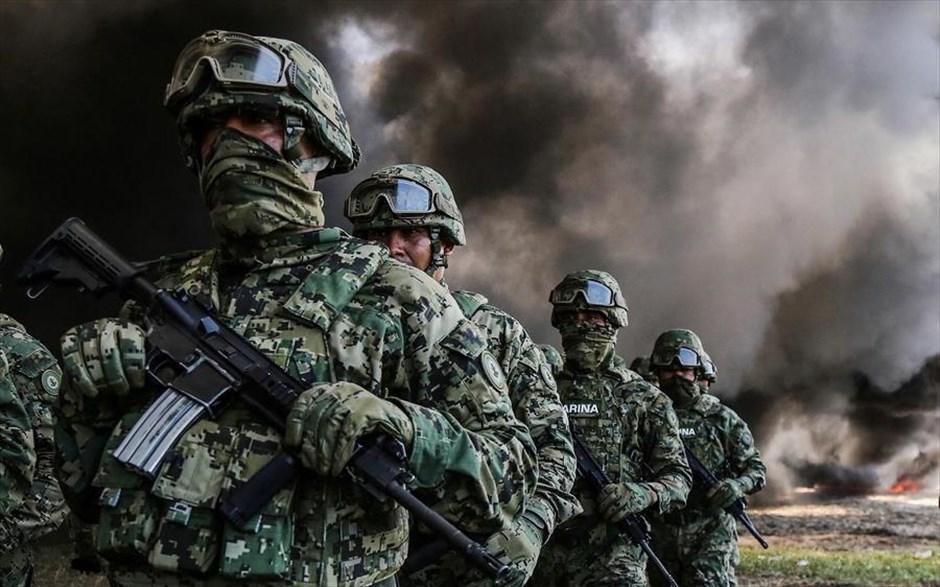 Παρασκευή, 21 Σεπτεμβρίου, Μεξικό. Ενοπλοι στρατιώτες μπροστά από μαύρο καπνό που αναδύεται από ναρκωτικά που καίγονται στο Ακαπούλκο