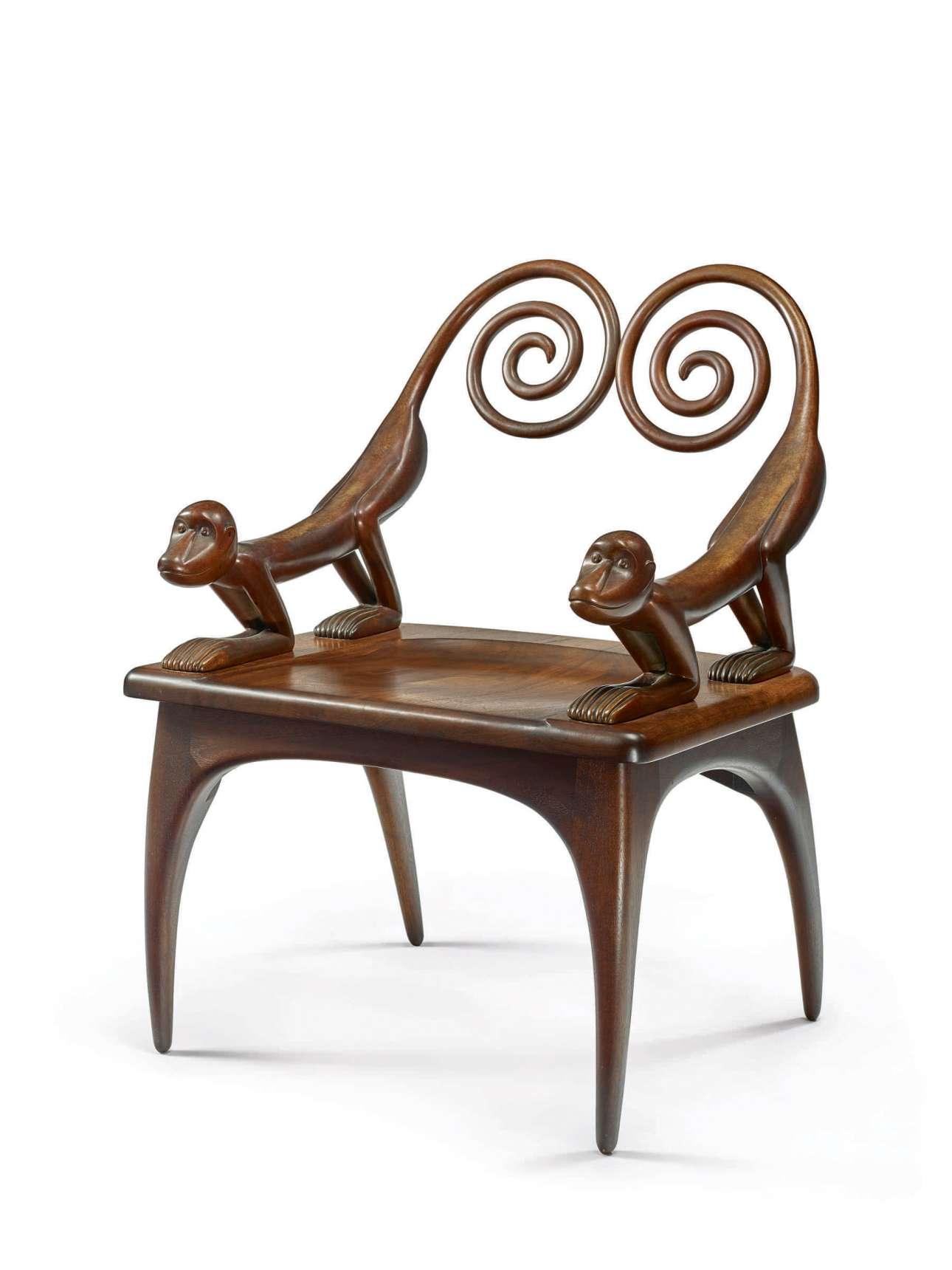 Ξύλινη καρέκλα με σκαλιστές μαϊμούδες σχεδιασμένη από την Τζούντι Κένσλι Μακί, η οποία μοιάζει σαν να έχει βγει από το «Τζουμάντζι»