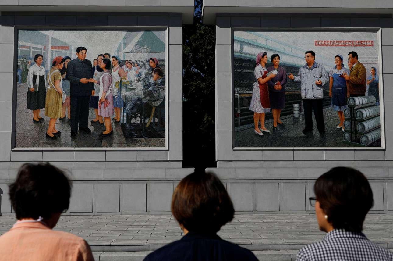 Γυναίκες στέκονται με δέος μπροστά σε πίνακες των θρυλικών ηγετών, έξω από εργοστάσιο μεταξιού στην Πιονγκγιάνγκ.