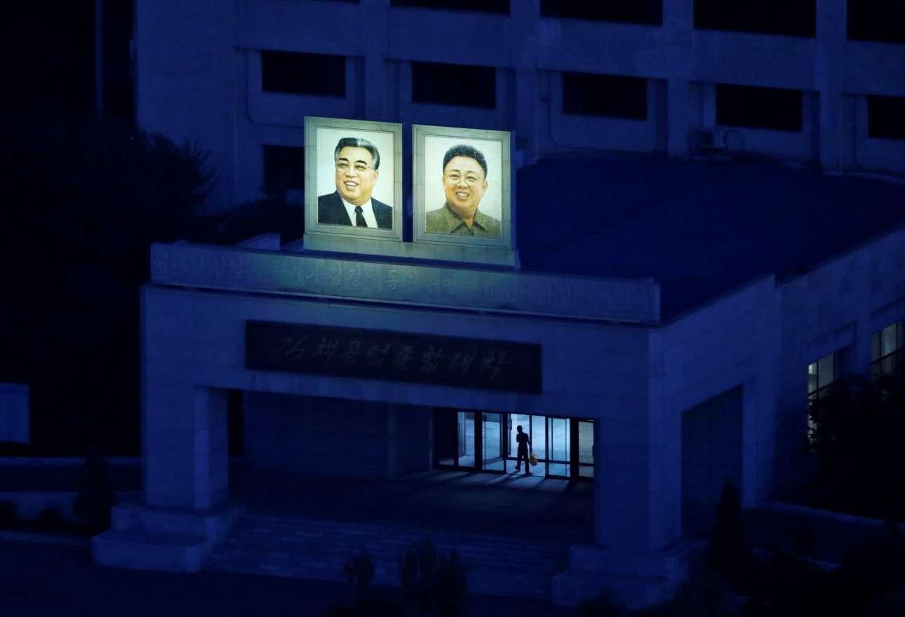 Μέσα στο σκοτάδι, λίγο πριν το ξημέρωμα, ξεχωρίζουν τα πορτρέτα των δύο Κιμ, έξω από το κτίριο του Πανεπιστημίου Τεχνολογίας Kim Chaek