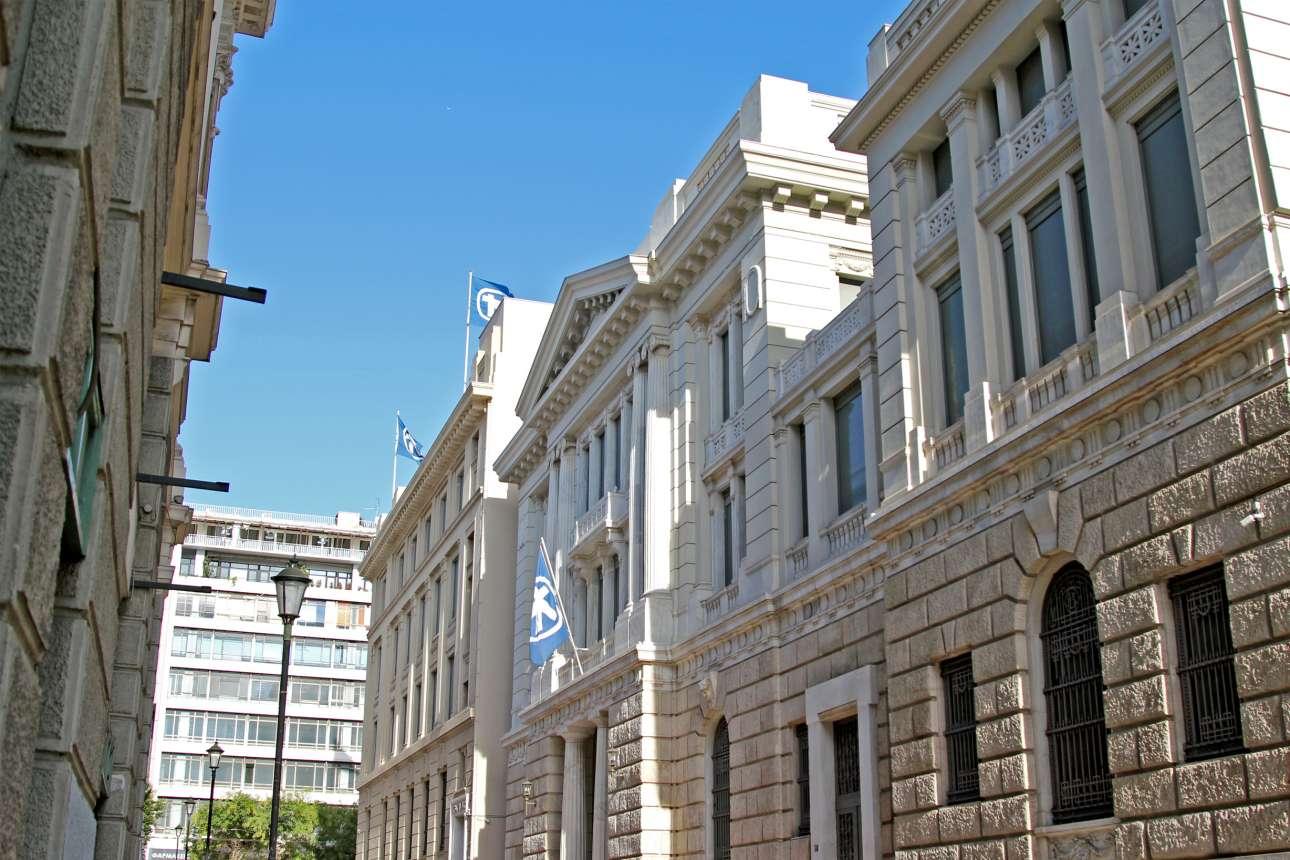 Στην οδό Πεσμαζόγλου, έναντι της Φιλεκπαιδευτικής Εταιρείας, βρίσκονται σε παράταξη οι προσόψεις των κτιρίων της Alpha Bank. Στο κέντρο, το κτίριο με το αέτωμα, χτίστηκε την περίοδο 1911-1916 σε σχέδια του Αναστασίου Μεταξά και θυμίζει ελληνική εκδοχή του βρετανικού Adam style