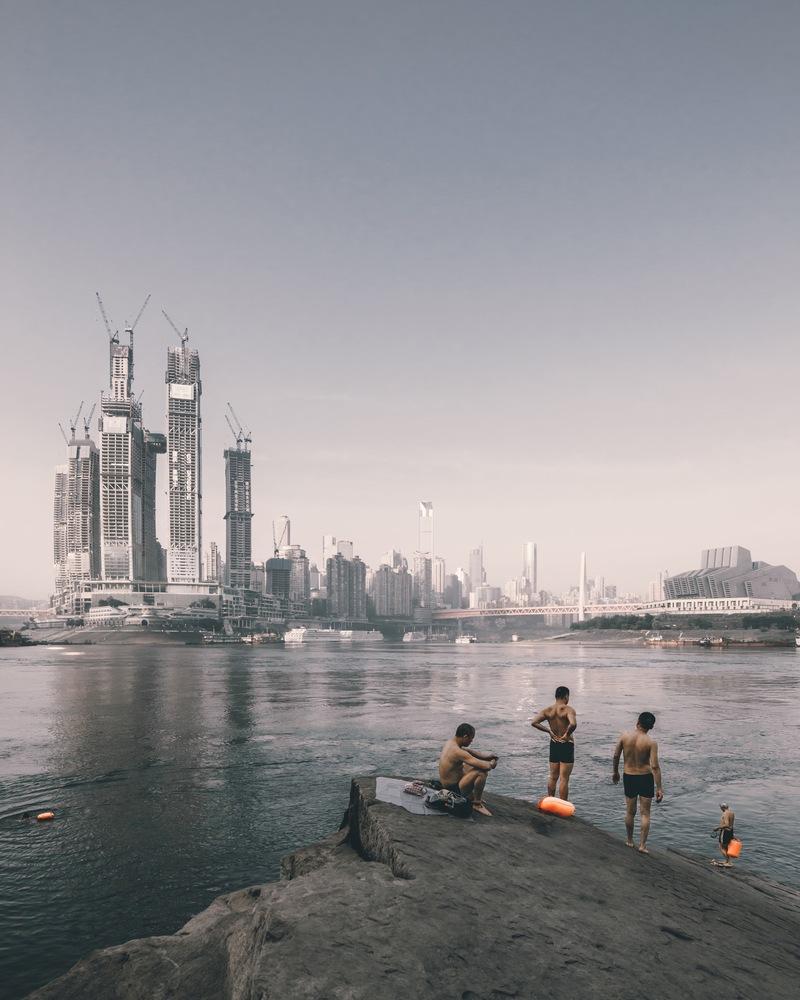Κολυμβητές στην όχθη του ποταμού απέναντι από την «Raffles City», σε σχέδια του γραφείου «Safdie Architects», στην πόλη Τσονγκκινγ της Κίνας