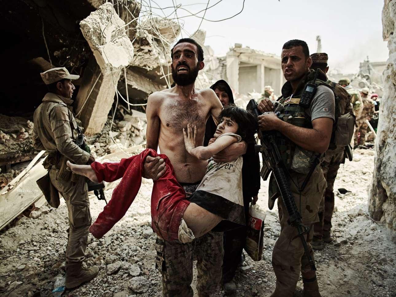 Βραβείο στην κατηγορία Ταξίδια και Περιπέτειες. Ενας συντετριμμένος πατέρας μεταφέρει τον τραυματισμένο γιο του, περνώντας από σημείο ελέγχου της δυτικής Μοσούλης στο Ιράκ