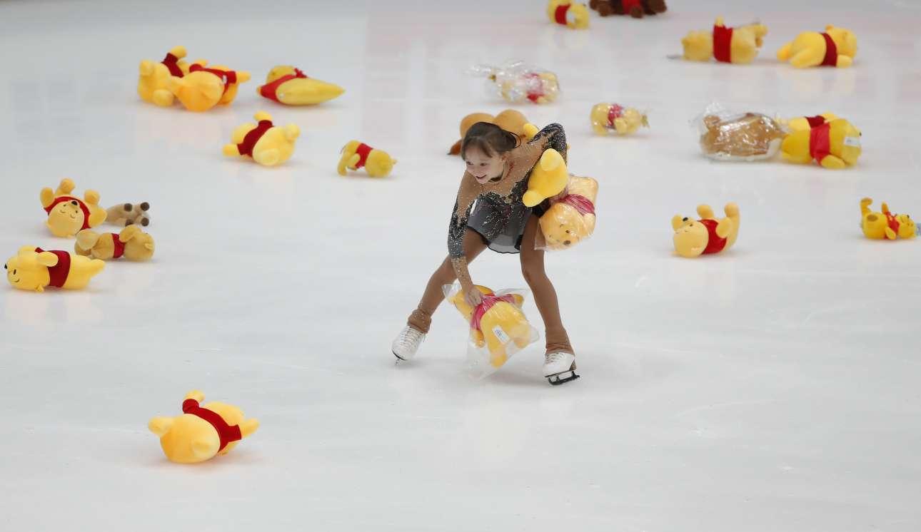Παρασκευή, 16 Νοεμβρίου, Ρωσία. Κορίτσι μαζεύει τα δώρα που πέταξαν στον πάγο οι θαυμαστές του Γιουζούρου Χάνιου, λίγο μετά την ολοκλήρωση του προγράμματός του, στο ISU Grand Prix Rostelecom Cup 2018 στη Μόσχα