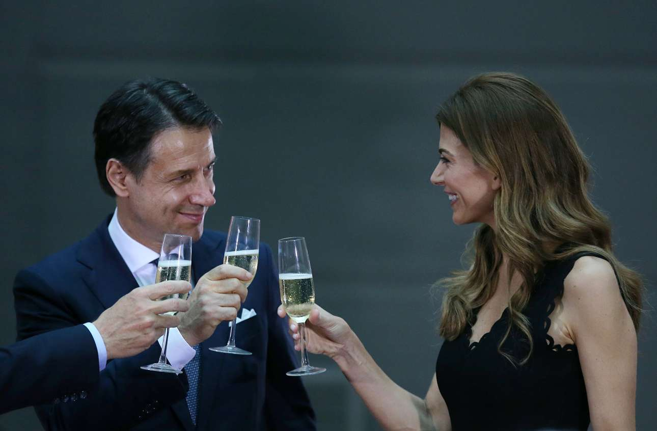 O πρωθυπουργός της Ιταλίας Τζουζέπε Κόντε τσουγκρίζει με την Πρώτη Κυρία της Αργεντινής Τζουλιάνα Αγουάντα