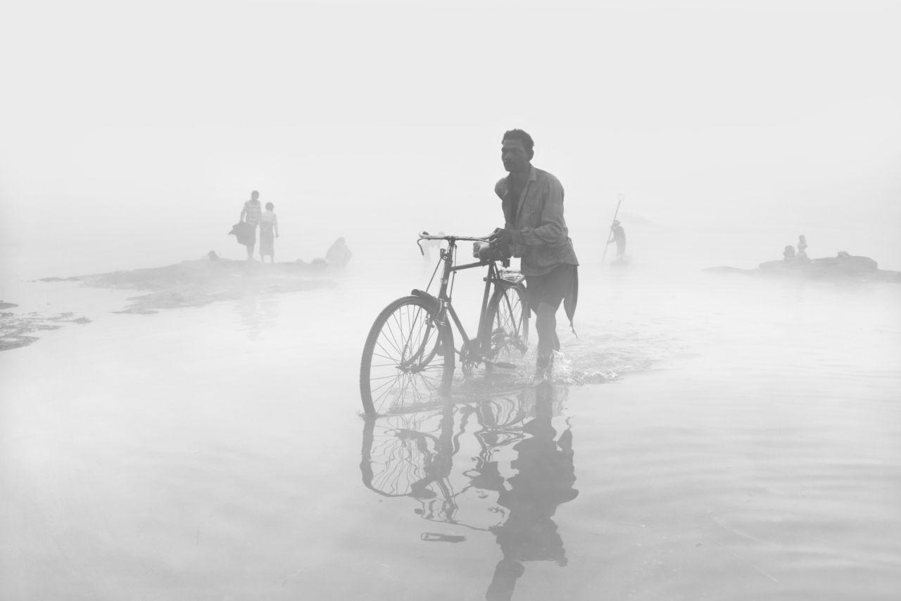 Ενας άνδρας με ποδήλατο περιπλανιέται μέσα στη βαριά ομίχλη που έχει καλύψει τη Μαντία Πραντές στην Ινδία