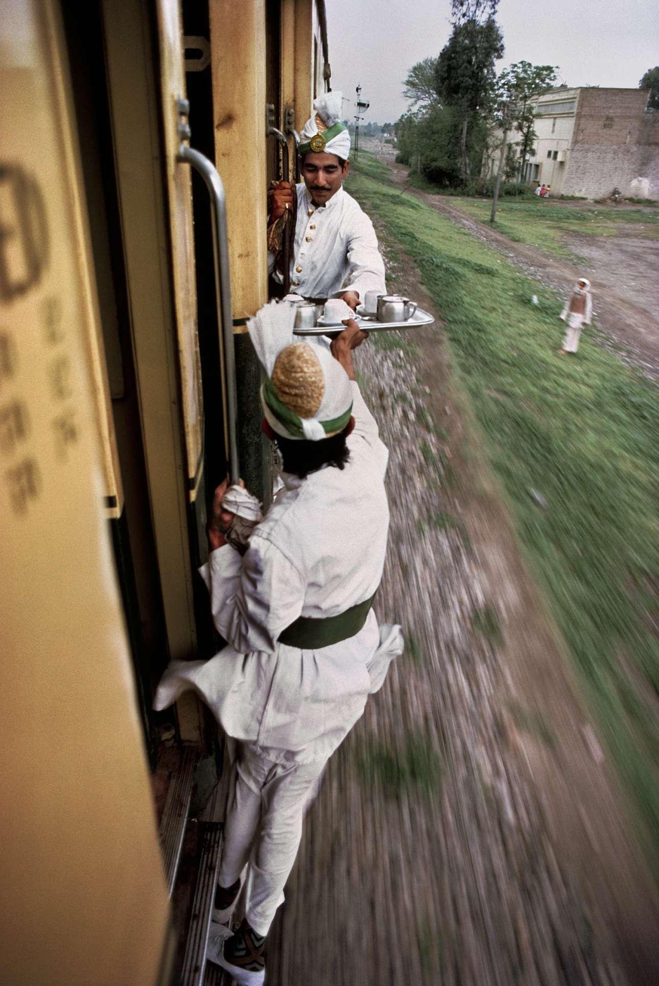 Σερβιτόροι διακινούν ένα δίσκο με τσάι ανάμεσα σε κινούμενα βαγόνια, στο Πακιστάν το 1983