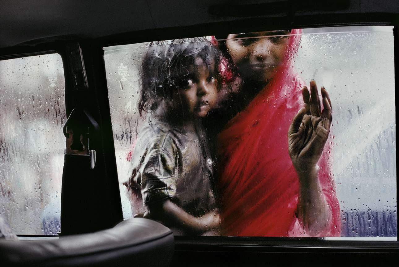 Μητέρα αγκαλιά με το παιδί της κοιτάζουν μέσα από παράθυρο ταξί στο Μουμπάι, το 1993. Η ινδική πόλη σφύζει από ζωή και εμπόριο, ωστόσο ο μισός πληθυσμός -από τα συνολικά 13 εκατομμύρια- ζει στους δρόμους ή σε καλύβες και χιλιάδες, όπως η γυναίκα της φωτογραφίας, επιβιώνουν ζητιανεύοντας