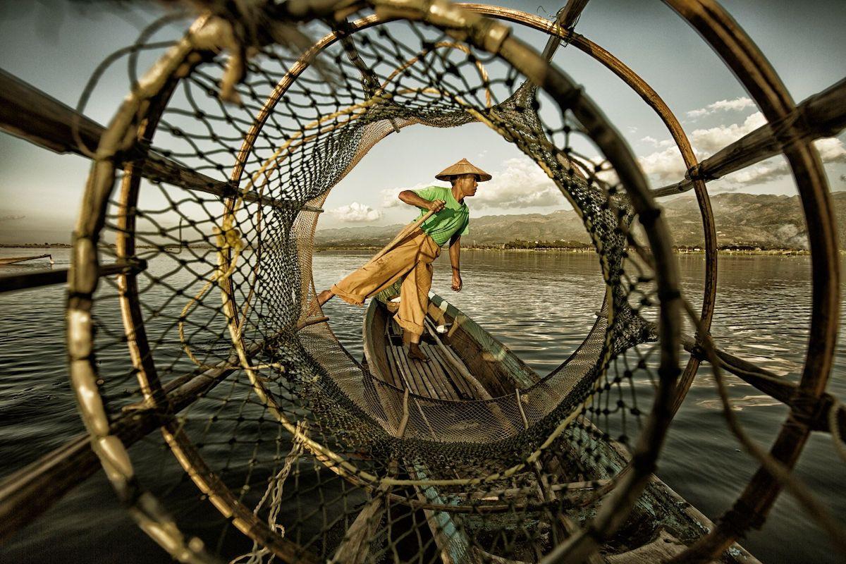 Βραβείο στην κατηγορία Κάτω των 20. «H λίμνη Inle της Μιανμάρ είναι καλυμμένη με καλάμια και φυτά, είναι δύσκολο να τραβάς κουπί καθιστός. Ως αποτέλεσμα, οι ψαράδες Intha έχουν αναπτύξει ένα ασυνήθιστο στυλ κωπηλασίας. Είναι εκπληκτικό το πώς οι άνθρωποι σε κάθε γωνιά του κόσμου βρίσκουν τρόπους να προσαρμοστούν στη φύση, αντλώντας έμπνευση από τη φύση» γράφει ο νεαρός φωτογράφος στο συνοδευτικό κείμενο
