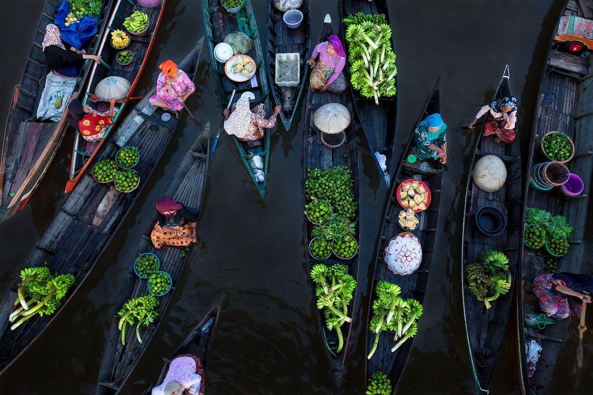 Βραβείο στην κατηγορία Χρώματα. «Πλωτό Παζάρι»: ξημερώματα στην πολύχρωμη αγορά Lok Baintan -μία από τις παλαιότερες αγορές της Ινδονησίας- όπου οι αγοραπωλησίες γίνονται μέσα από παραδοσιακές ξύλινες βάρκες