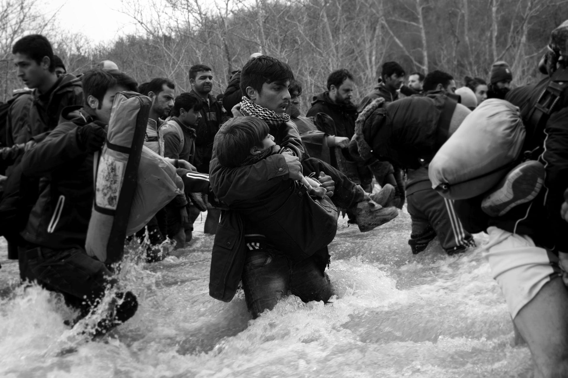 Πρόσφυγες και μετανάστες από τον αυτοσχέδιο καταυλισμό στην Ειδομένη διασχίζουν ένα παγωμένο ποτάμι σε μία προσπάθεια να περάσουν τα κλειστά σύνορα προς την ΠΓΔΜ