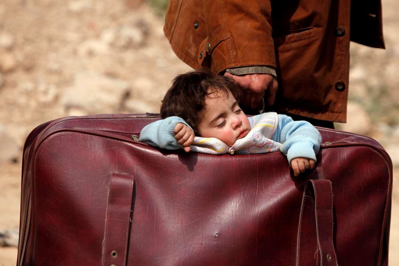 15 Μαρτίου. Ενα μικρό παιδί κοιμάται μέσα σε βαλίτσα καθώς άμαχοι πολίτες εγκαταλείπουν την πόλη Χαμουρίγιε στην Ανατολική Γούτα της Συρίας