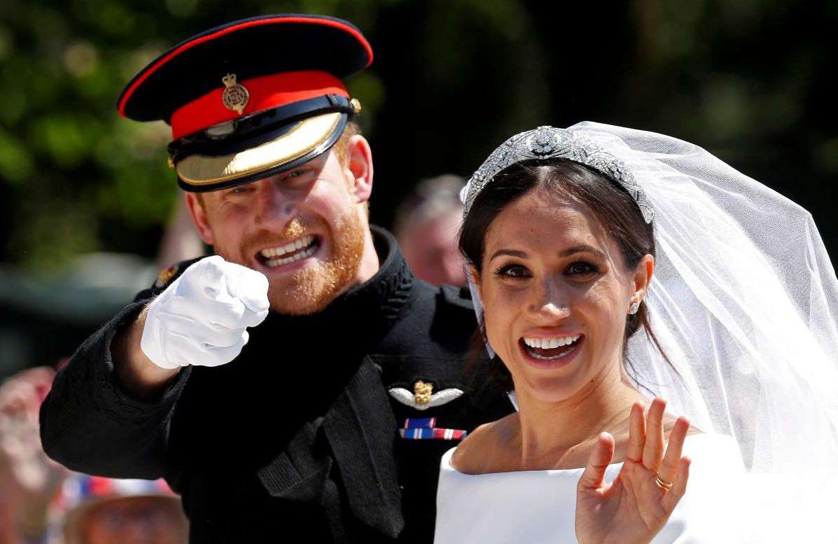 19 Μαΐου. Οι νεόνυμφοι πρίγκιπας Χάρι και Μέγκαν Μαρκλ χαιρετούν το πλήθος πάνω από την άμαξα που τους μεταφέρει, μετά τον γάμο τους στο κάστρο Ουίνδσορ
