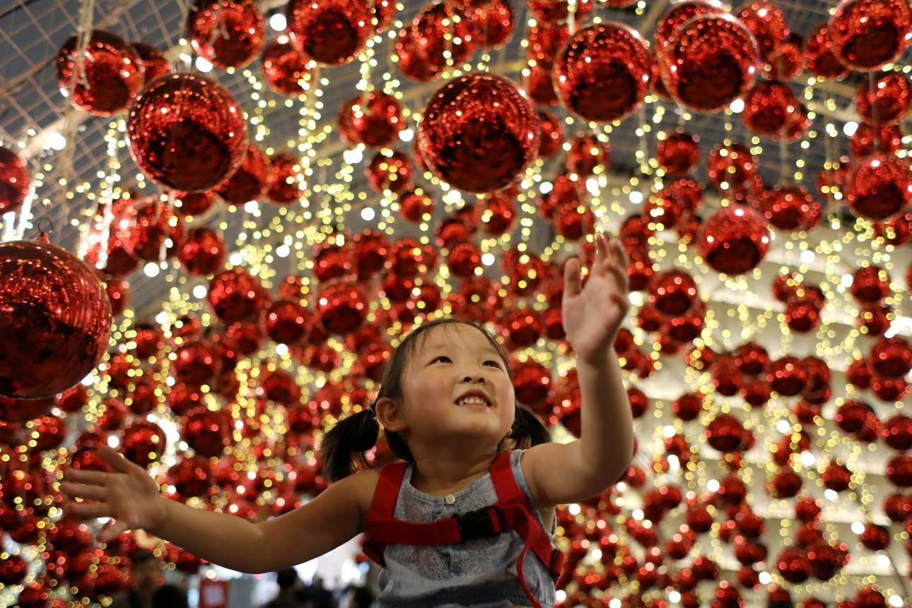 Κοριτσάκι επεξεργάζεται γεμάτο ενθουσιασμό τη χριστουγεννιάτικη διακόσμηση, σε εμπορικό κέντρο της Μπανγκόκ