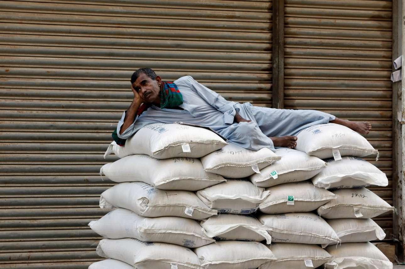 Τετάρτη, 5 Δεκεμβρίου, Πακιστάν. Εργάτης ξεκουράζεται πάνω σε ένα σωρό από σακιά με ζάχαρη καθώς περιμένει να ανοίξει η αγορά στο Καράτσι