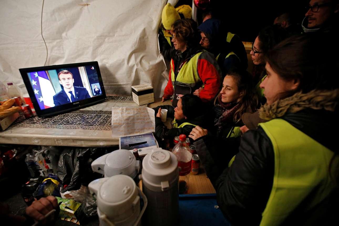 Τρίτη, 11 Δεκεμβρίου, Γαλλία. Διαδηλωτές από το κίνημα των Κίτρινων Γιλέκων παρακολουθούν στην Λα Σιοτά, κοντά στη Μασσαλία, το διάγγελμα του γάλλου προέδρου Εμανουέλ Μακρόν