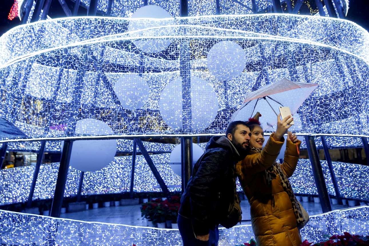 Τετάρτη, 12 Δεκεμβρίου, Ελλάδα. Ένα ζευγάρι φωτογραφίζεται μπροστά από το χριστουγεννιάτικο δέντρο στο Σύνταγμα