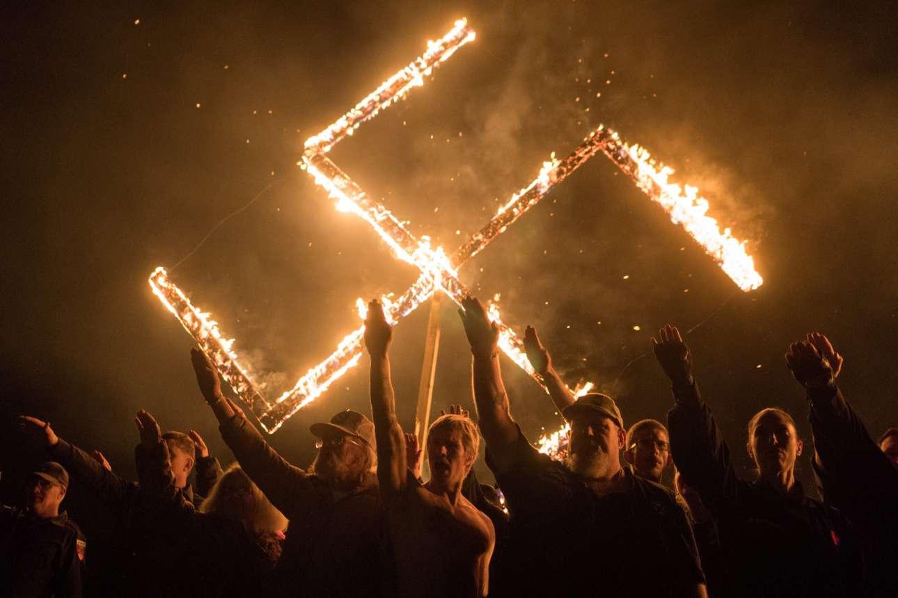 21 Απριλίου. Υποστηρικτές του Εθνικού Σοσιαλιστικού Κινήματος, μιας λευκής εθνικιστικής πολιτικής ομάδας, χαιρετούν ναζιστικά μπροστά από μία φλεγόμενη σβάστικα, στην Τζόρτζια των ΗΠΑ