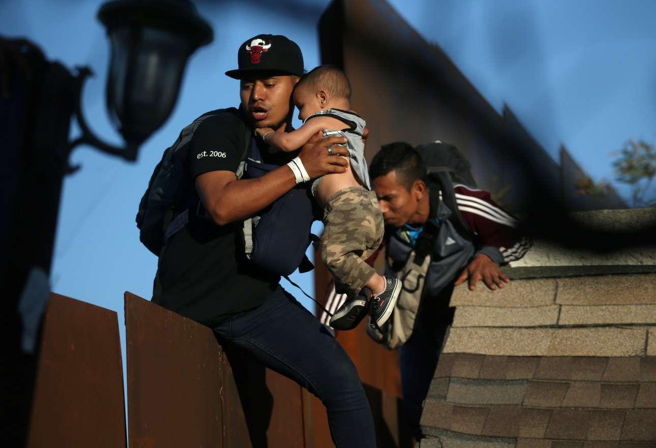 Παρασκευή, 14 Δεκεμβρίου, Μεξικό. Οικογένεια μεταναστών προσπαθεί να περάσει το τείχος στη συνοριακή περιοχή της Τιχουάνα, για να εισέλθει στις ΗΠΑ