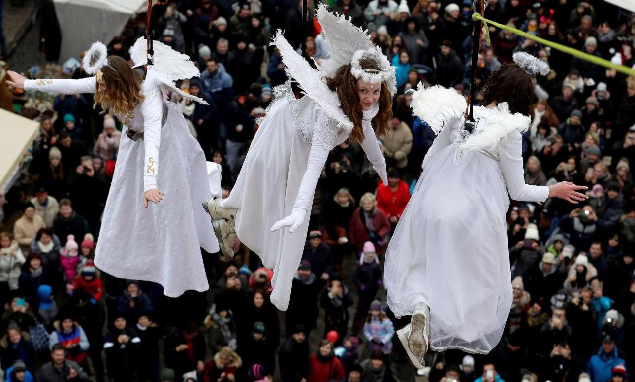 Τρεις γυναίκες ντυμένες άγγελοι αιωρούνται πάνω από την υπαίθρια χριστουγεννιάτικη αγορά της Γιουστέκ, στην Τσεχία