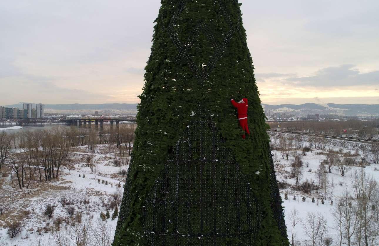 Ενας θαρραλέος Αϊ-Βασίλης στολίζει το χριστουγεννιάτικο δέντρο 57 μέτρων στη σιβηρική πόλη Κρασνογιάρσκ, στη Ρωσία