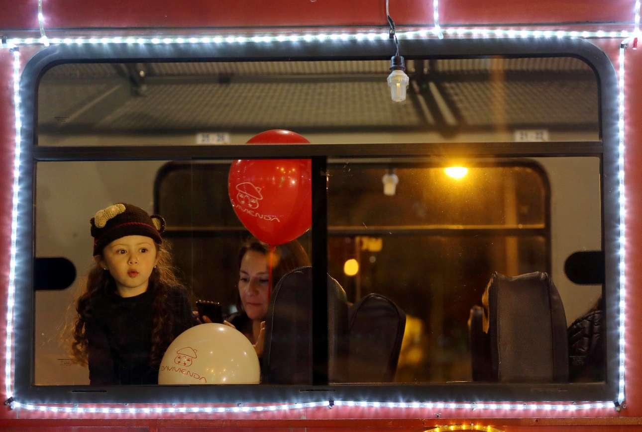Το κοριτσάκι κοιτάζει έξω από τουριστικό τρένο που έχει «φορέσει» τα γιορτινά του στη Μπογκοτά, στην Κολομβία