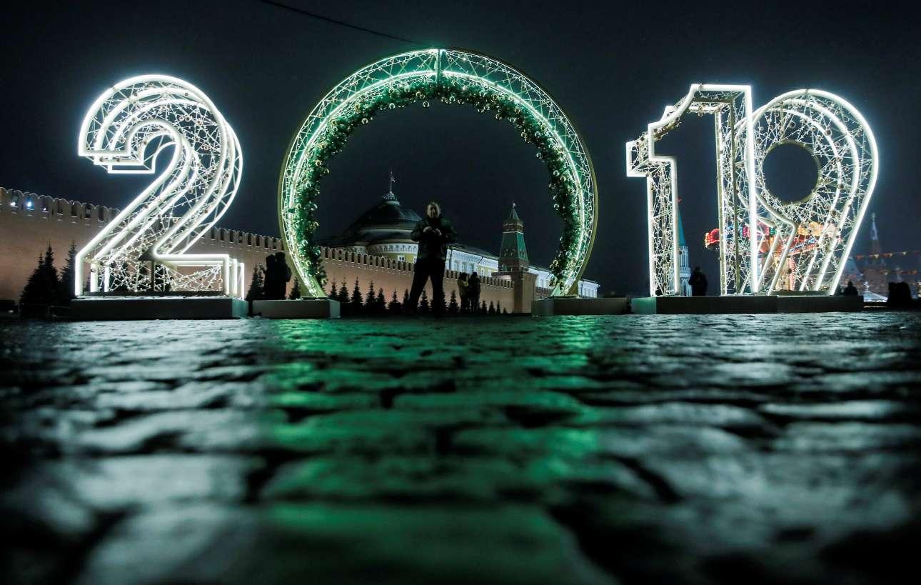 Ανδρας ποζάρει κάτω από μία μεγάλη επιγραφή που γράφει 2019, η οποία κοσμεί την Κόκκινη Πλατεία της Μόσχας