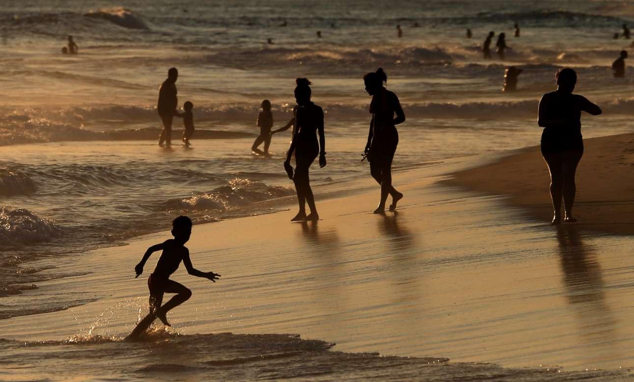 Τετάρτη, 19 Δεκεμβρίου, Βραζιλία. Κόσμος απολαμβάνει το μπάνιο του στην παραλία Barra da Tijuca, στο Ρίο ντε Τζανέιρο