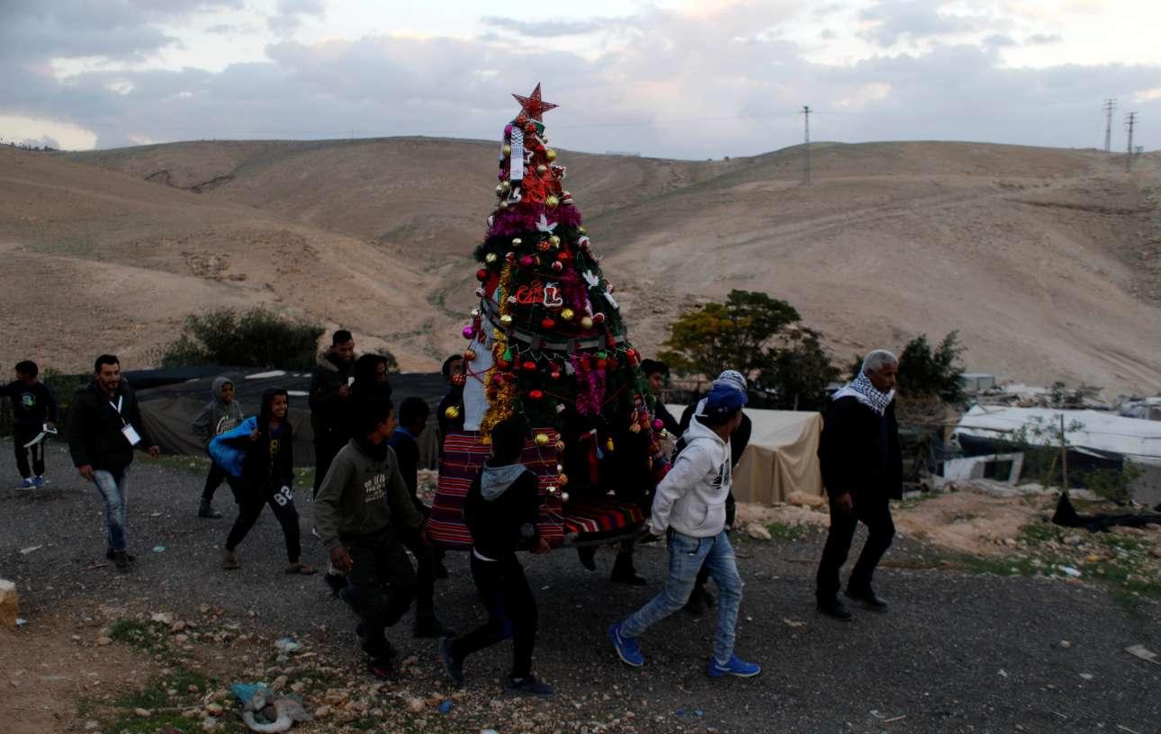 Πέμπτη, 20 Δεκεμβρίου, Δυτική Οχθη. Παλαιστίνιοι κουβαλούν ένα στολισμένο χριστουγεννιάτικο δέντρο στο χωριό Βεδουίνων, Khan al-Ahmar