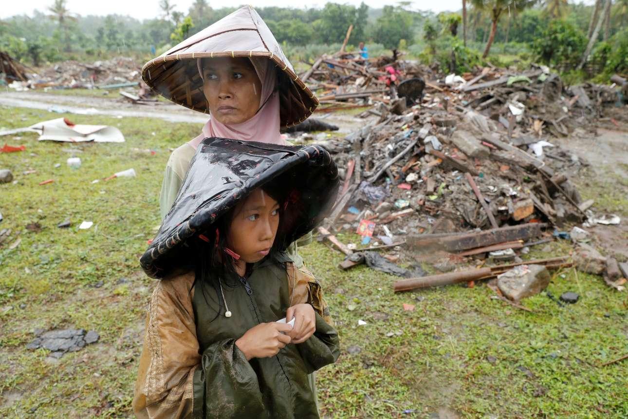 Τετάρτη, 26 Δεκεμβρίου, Ινδονησία. Μία γυναίκα και ένα κοριτσάκι ανάμεσα σε συντρίμμια στο χωριό Σουμούρ, στην επαρχία Μπάντεν της Ινδονησίας. Από το τσουνάμι που έπληξε την Κυριακή τις νήσους Ιάβα και Σουμάτρα, 429 άνθρωποι έχουν χάσει τη ζωή τους, περισσότεροι από 1.400 έχουν τραυματιστεί και χιλιάδες έχουν μείνει άστεγοι