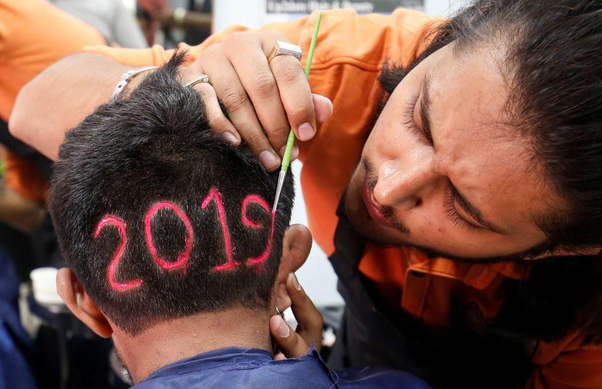 Ινδός κομμωτής χρωματίζει το 2019 στο κεφάλι του πελάτη του, λίγες ώρες πριν την αλλαγή του χρόνου