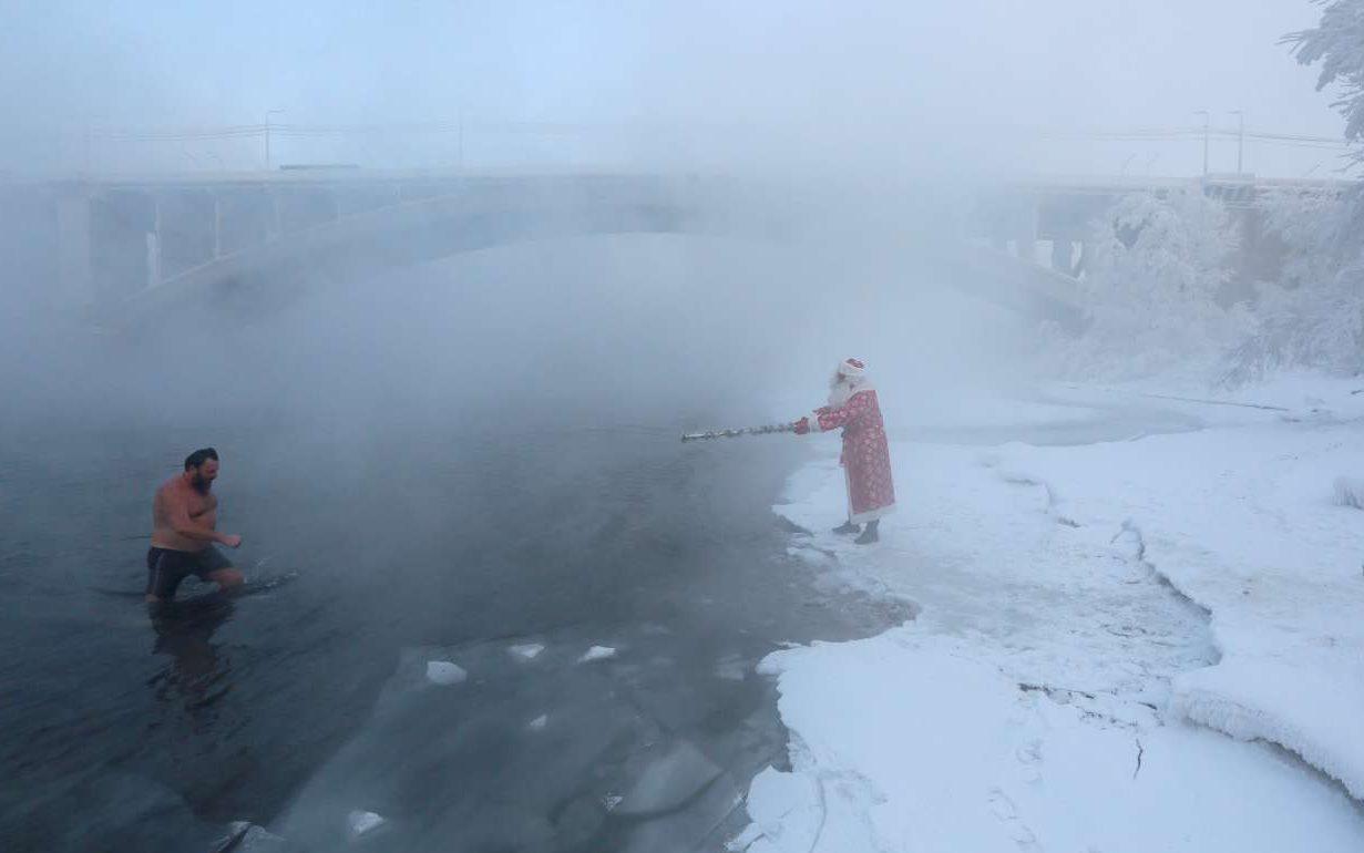 Ο Παππούς Χιονιάς, ο αντίστοιχος Αγιος Βασίλης της Ρωσίας, συγχαίρει τον θαρραλέο κολυμβητή που βούτηξε στα νερά του ποταμού Γενισέι, στο Κρασνογιάρσκ, αψηφώντας τους 26 βαθμούς υπό το μηδέν