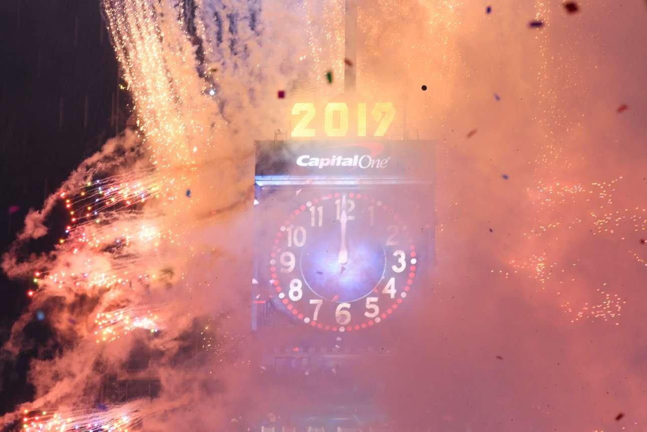 To ρολόι της εμβληματικής Τάιμς Σκουέαρ στη Νέα Υόρκη δείχνει 12 τα μεσάνυχτα και πνίγεται σε πυροτεχνήματα