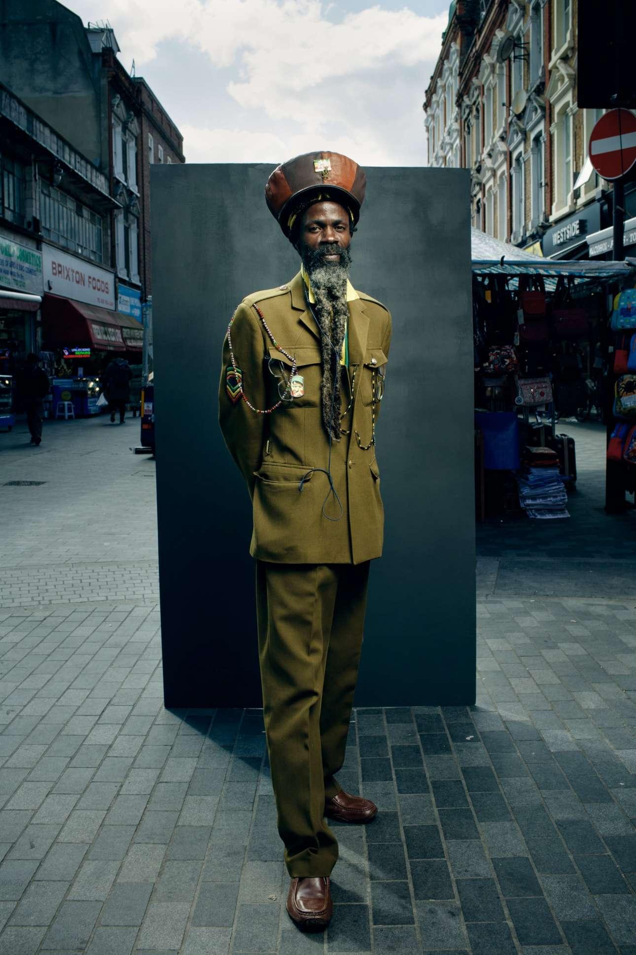 Ο Πας ποζάρει με φόντο την πολύχρωμη περιοχή Μπρίξτον του Λονδίνου