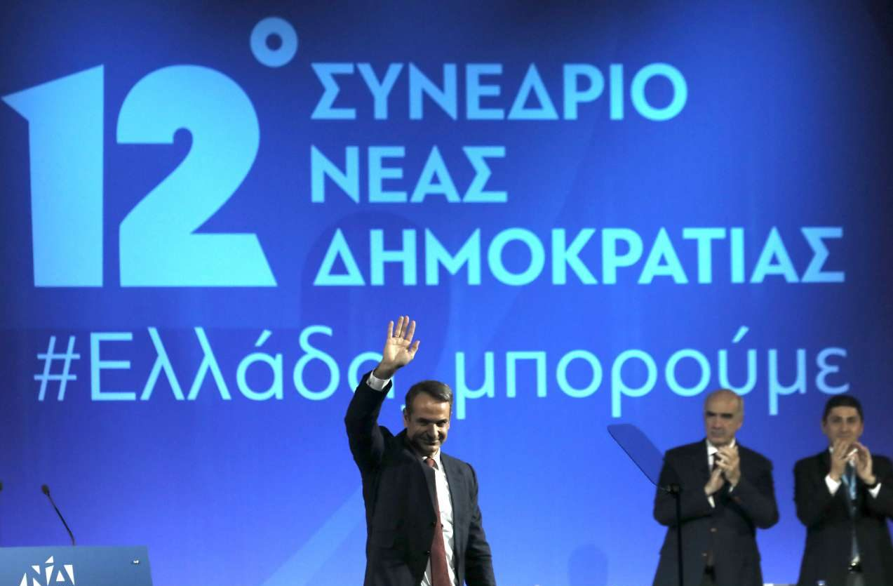 O Kυριάκος Μητσοτάκης χαιρετά τους συνέδρους με το σύνθημα του #Eλλάδα Μπορούμε να δεσπόζει πίσω του. Στο βάθος δεξιά, οι Βαγγέλης Μεϊμαράκης και Λευτέρης Αυγενάκης