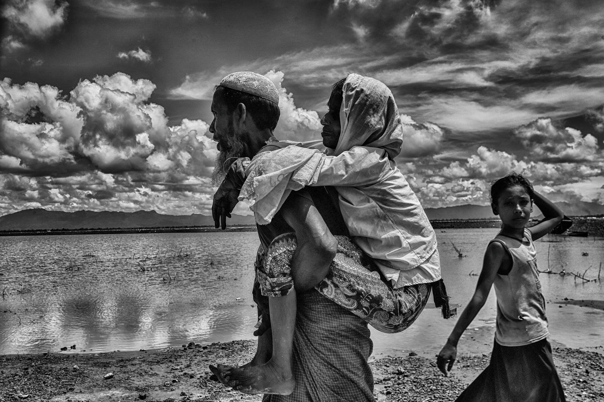 Ο 65χρονος Ροχίνγκια Αχμέντ κουβαλάει στην πλάτη του την μητέρα του Φατίμα 95 ετών προς το Μπανγκλαντές, αφού έχουν εγκαταλείψει τη Μιανμάρ. «Πολλοί από αυτούς που διαφεύγουν είναι αγρότες που είχαν μία απλή ζωή και ήθελαν να ζήσουν ειρηνικά με τους δικούς τους όρους, με σεβασμό, αξιοπρέπεια και με τη δική τους ταυτότητα. Ο καθένας έχει το δικαίωμα να ζει και να ακολουθεί τα πιστεύω του και τη θρησκεία του» λέει ο φωτογράφος