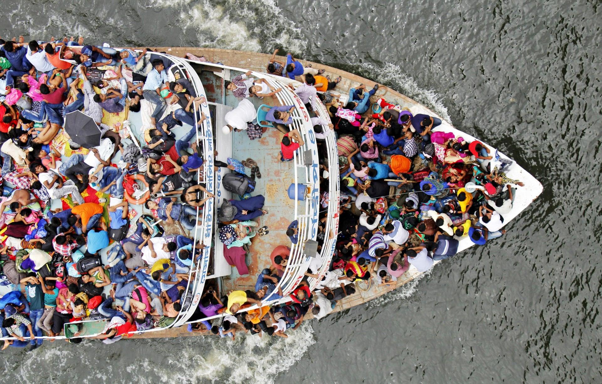 «Εσωτερικοί μετανάστες», στιβαγμένοι σε ένα πλοίο, διασχίζουν τον ποταμό Dhaleshwari στη Ντάκα του Μπαγκλαντές, πηγαίνοντας από την πρωτεύουσα στα σπίτια τους για να γιορτάσουν το μουσουλμανικό Εΐντ μαζί με τις οικογένειες τους