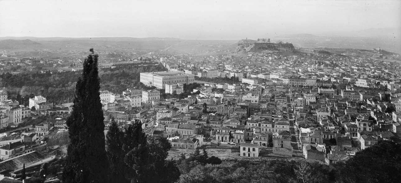 Αποψη της Αθήνας από τους πρόποδες του Λυκαβηττού. Διακρίνονται τα Παλαιά Ανάκτορα με την πλατεία Συντάγματος και την Ακρόπολη στο βάθος. Αριστερά η λεωφόρος Βασ. Σοφίας με τα νεοκλασικά μέγαρα. Σε πρώτο πλάνο η περιοχή του Κολωνακίου με διακριτή την οδό Βουκουρεστίου. Λίγο πριν την κατάληξή της, στα δεξιά, το Ιλίου Μέλαθρον