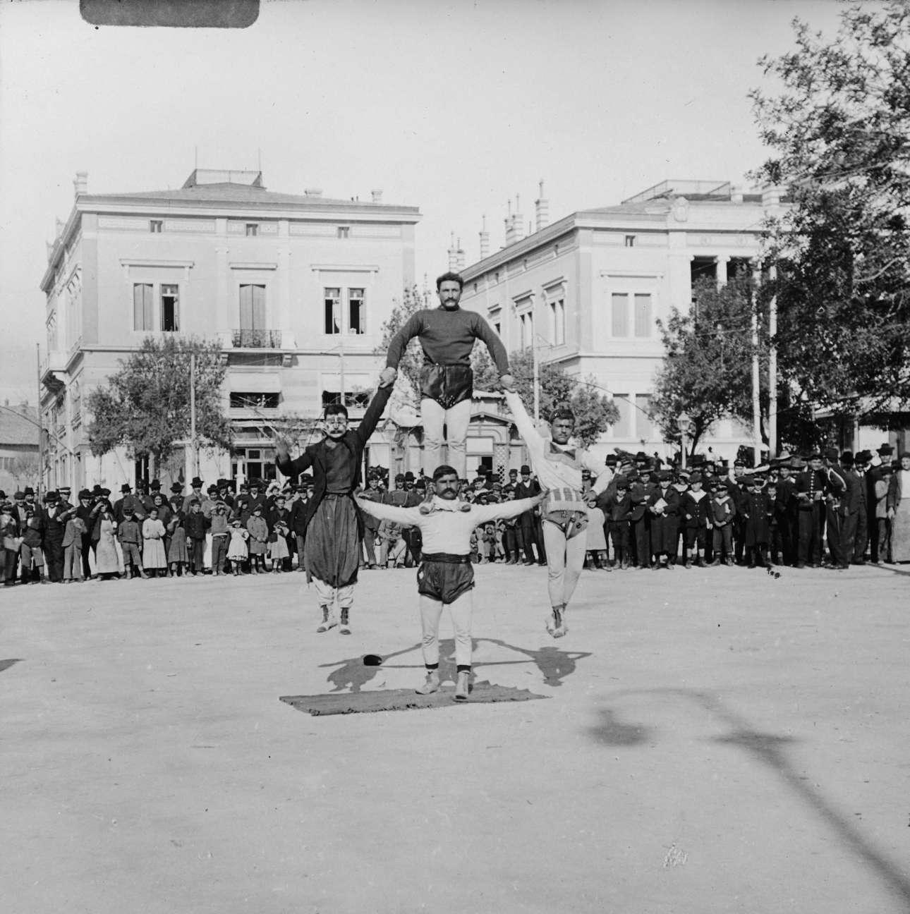 Ακροβάτες στην πλατεία Συντάγματος. Στο βάθος διακρίνονται τα μέγαρα Ιωάννου Βούρου και Στεφάνου Σκουλούδη