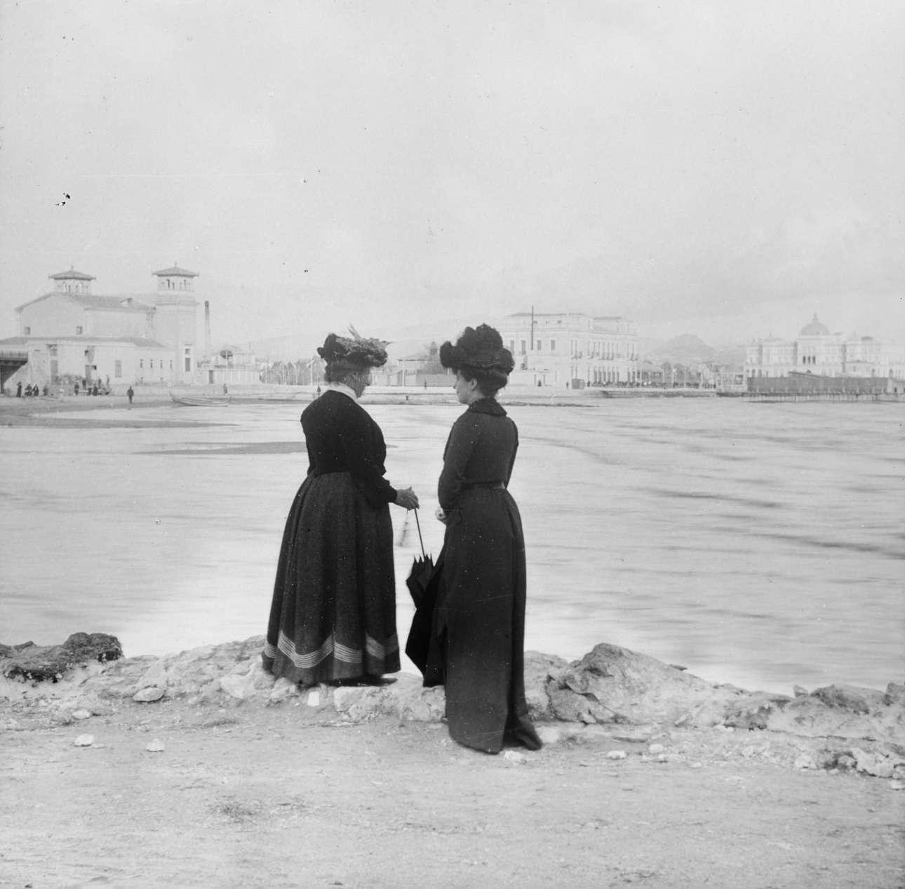 Γυναίκες στο Νέο Φάληρο. Στο βάθος διακρίνονται, από αριστερά προς δεξιά, το νέο θέατρο που κτίσθηκε το 1896, το ξενοδοχείο του σταθμού με την προσθήκη του τρίτου ορόφου, το νεόδμητο ξενοδοχείο «Ακταίον» και η εξέδρα με τις καμπίνες των θαλάσσιων λουτρών