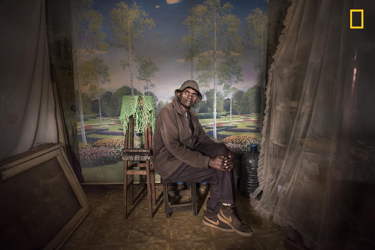 Πρώτη θέση στην κατηγορία Ανθρωποι. Πορτρέτο του Ντέιβιντ Μουγιοτσοκέρα τραβηγμένο την τελευταία του μέρα ως εργαζόμενος στο φωτογραφείο Weekend Studio, στην πόλη Κιμπέρα της Κένυας. Ο Ντέιβιντ δούλεψε 37 χρόνια εκεί, αλλά εξαιτίας των κινητών με κάμερα οι υπηρεσίες του δεν είχαν μεγάλη ζήτηση τον τελευταίο καιρό. Προβληματισμένη από το κλείσιμο του φωτογραφείου, η φωτογράφος Μία Κόλις ανέλαβε το ενοίκιο και κρέμασε εκεί πορτρέτο του Ντέιβιντ προς τιμήν του