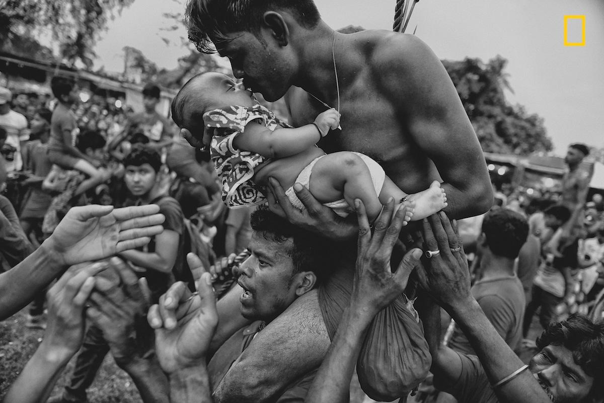 Τρίτη θέση στην κατηγορία Ανθρωποι. Ινδουιστής φιλάει το νήπιο μωρό του κατά τη διάρκεια του φεστιβάλ Charak Puja στη Δυτική Βεγγάλη της Ινδίας. Η παράδοση απαιτεί από τον πιστό να τρυπηθεί με έναν γάντζο και να κρεμαστεί από σχοινί. Αυτή η οδυνηρή πρακτική έχει θεσπιστεί για να σώσει τα παιδιά των Ινδουιστών από το άγχος. Ο φωτογράφος καταφέρνει να αιχμαλωτίσει την αγάπη και την ανησυχία που νιώθει ένας πατέρας για τον γιο του