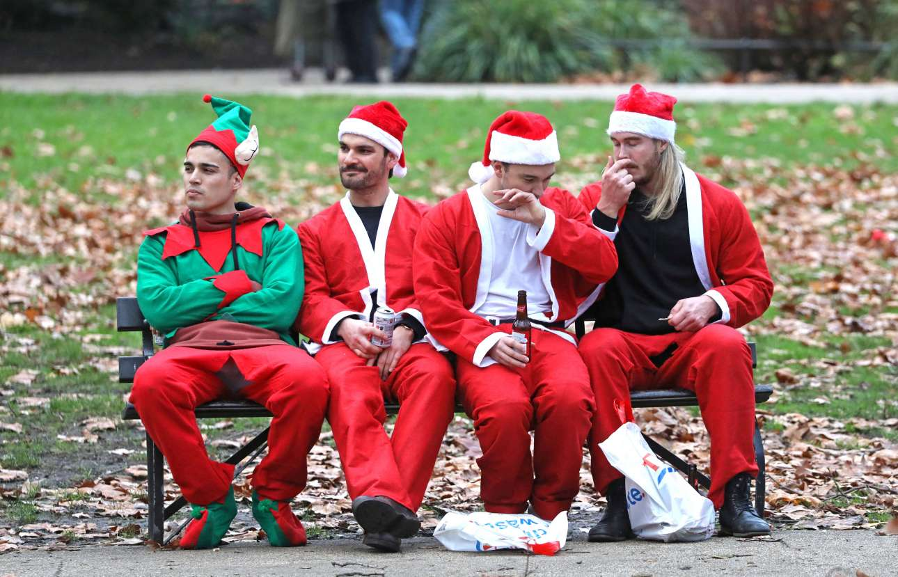 Σάββατο, 8 Δεκεμβρίου, Αγγλία. Αγιοι Βασίληδες (ο Θεός να τους κάνει) με μπύρες σε ένα παγκάκι κάνουν διάλειμμα από SantaCon που έγινε και φέτος στο κεντρικό Λονδίνο