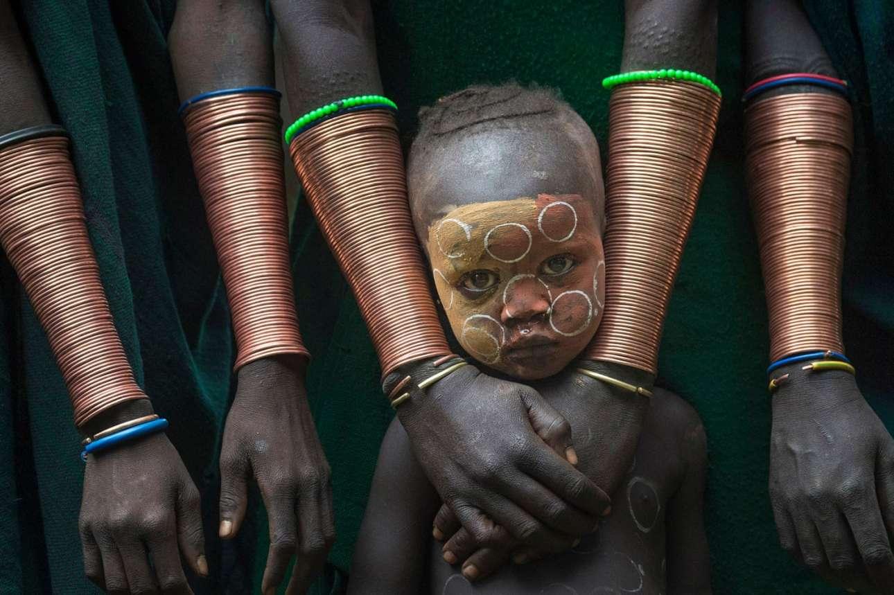 Βραβείο στην κατηγορία Πρόσωπα, Ανθρωποι και Πολιτισμός. Αγόρι από τη φυλή Σούρι που ζει στην κοιλάδα Ομο της Αιθιοπίας, προστατευμένο από γυναίκες της φυλής με τα χαρακτηριστικά μακριά χάλκινα βραχιόλια
