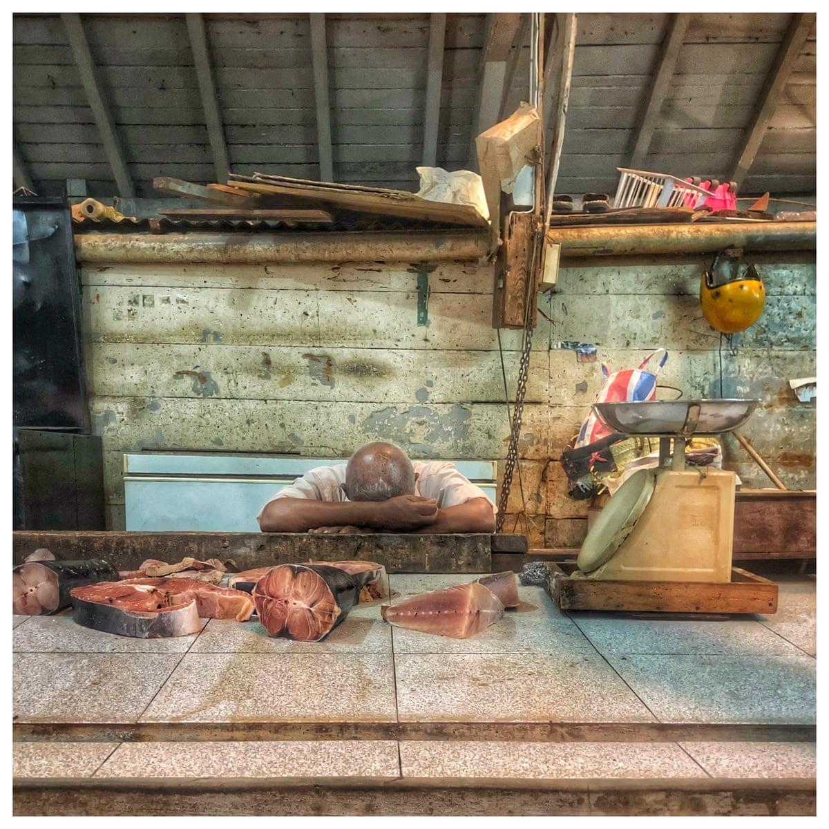 Βραβείο στην κατηγορία Smart (φωτογραφία τραβηγμένη από κινητό ή τάμπλετ). Ψαροπώλης κάνει διάλειμμα στην αγορά του Πορ Λουί στον Μαυρίκιο: μία στιγμή ηρεμίας μετά το πέρασμα του κυκλώνα Berguitta που σάρωσε τη χώρα