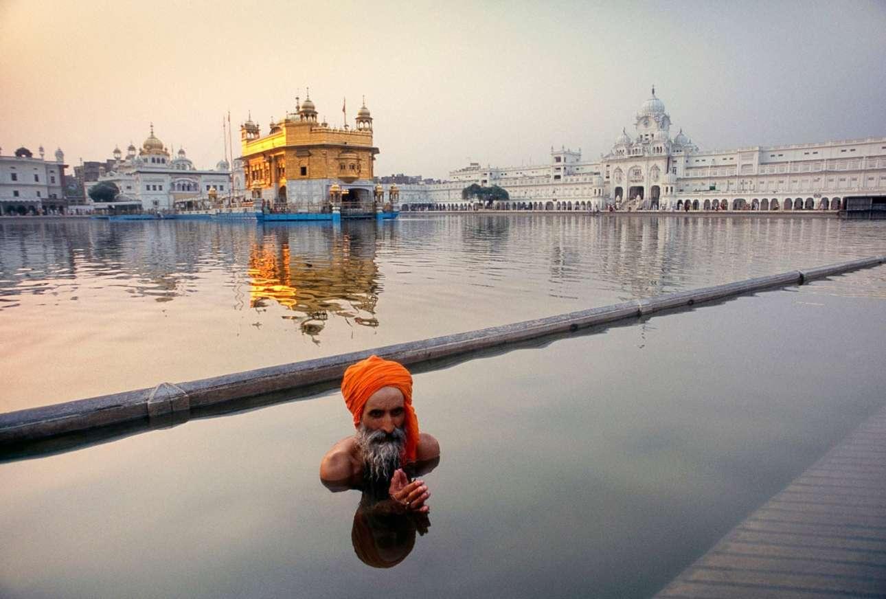 Βραβείο στην κατηγορία Ταξιδιωτικό Πορτφόλιο. Προσκυνητής Σιχ κάνει μπάνιο στην ιερή πισίνα Amrit Sarovar, μπροστά από το Χρυσό Ναό του Αμριτσάρ στην Ινδία