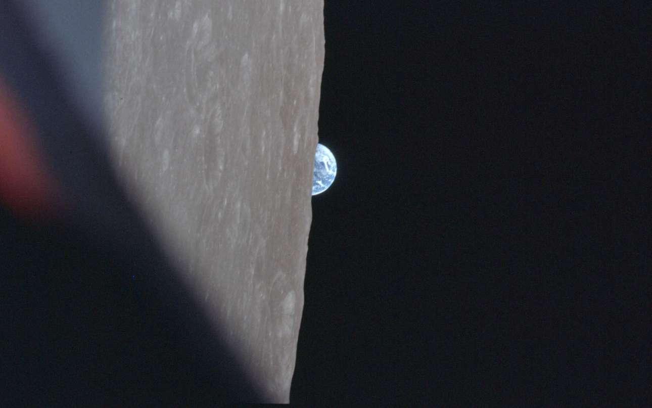 Μία κάθετη λήψη της επιφάνειας της Σελήνης και στο φόντο η Γη που ανατέλλει πάνω από τον σεληνιακό ορίζοντα