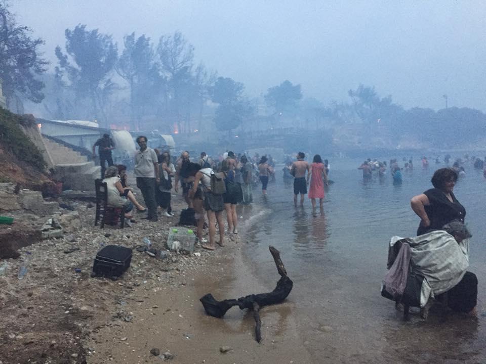 24 Ιουλίου. Ανθρωποι έχουν βουτήξει στη θάλασσα για να σωθούν από την πυρκαγιά στο Μάτι, σε μία τραγική εικόνα που φέρνει μνήμες από άλλες εποχές