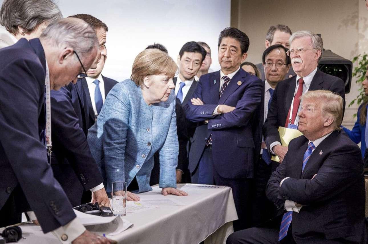 9 Ιουνίου. Μία εικόνα, χίλιες λέξεις... Μία ιστορική αποτύπωση του κλίματος που επικρατούσε στη Σύνοδο Κορυφής του G7 στον Καναδά και της διεθνούς απομόνωσης των ΗΠΑ επί Τραμπ: Ο αμερικανός πρόεδρος καθισμένος σε μια καρέκλα με σταυρωμένα τα χέρια και περιτριγυρισμένος ως και στριμωγμένος από τους υπόλοιπους ηγέτες, με τη φιγούρα της Ανγκελα Μέρκελ να δεσπόζει