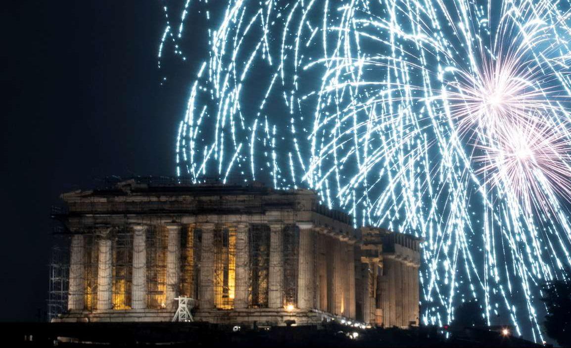 Πυροτεχνήματα δίνουν άλλο χρώμα στον ουρανό πάνω από τον Παρθενώνα καθώς η Αθήνα υποδέχτηκε το νέο έτος υπό βροχή